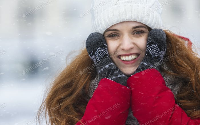 Pretty smiling girl enjoying beautiful winter in city