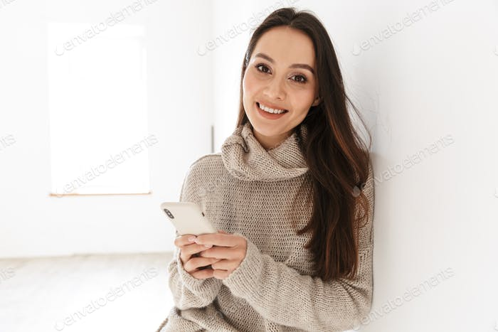 Image of asian woman smiling and using smartphone while leaning on wall