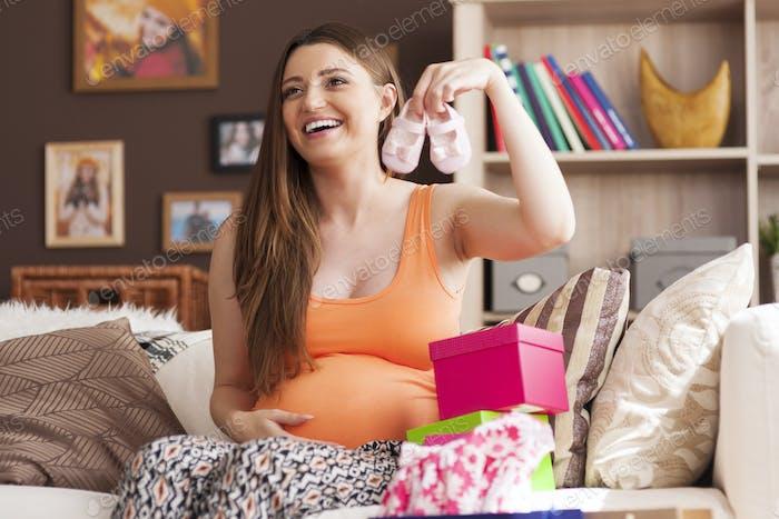 Feliz mujer embarazada mostrando compras exitosas para niña