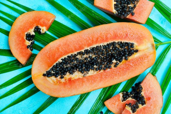 Frische Papaya-Frucht auf Palmblatt. Grauer Steinhintergrund. Draufsicht.