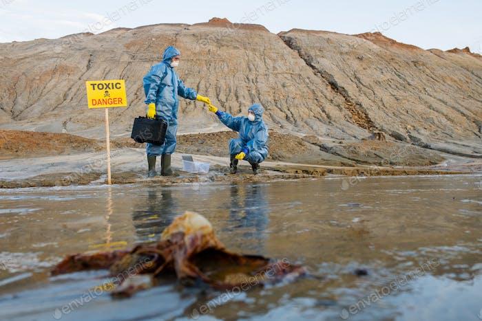 Ökologe übergeben Probe von toxischem Wasser oder Boden an Kollegen während der Forschung