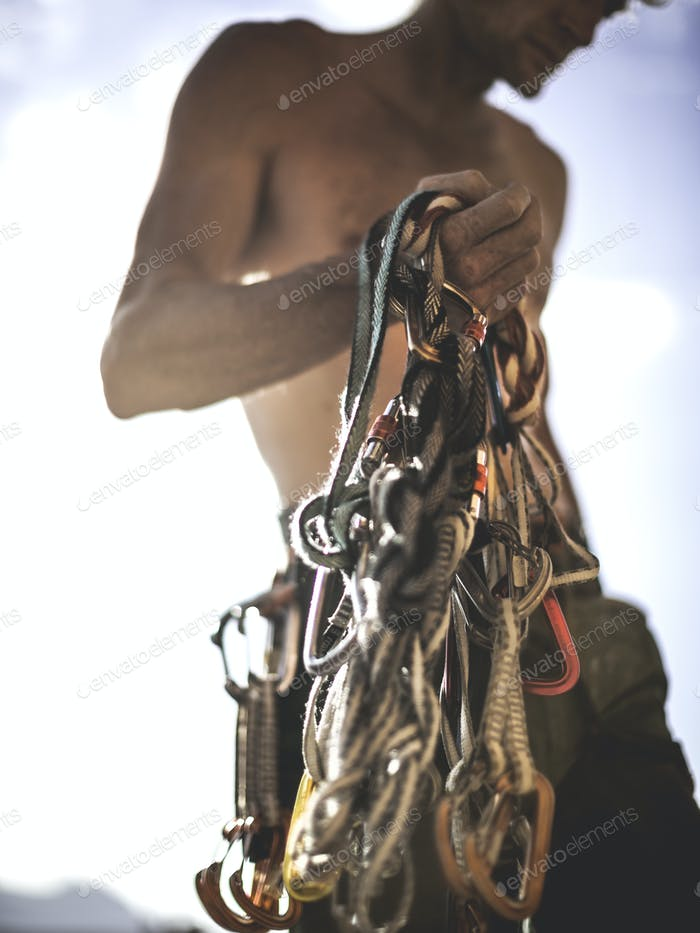 Close up of a climber holding a bundle of rope and carabiners, climbing equipment.
