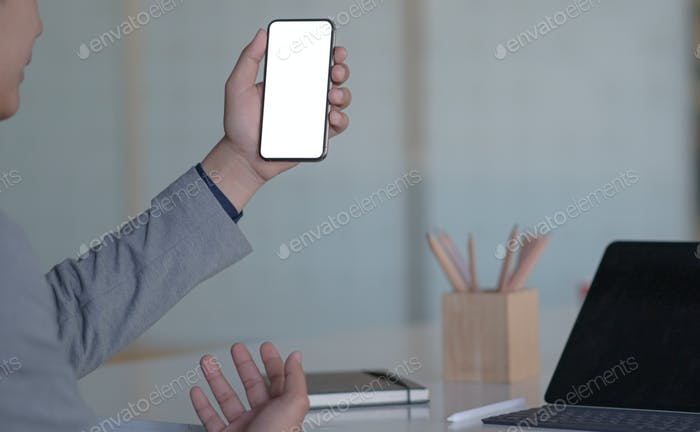 Young executive holds a smartphone for online video calling in a modern personal office.