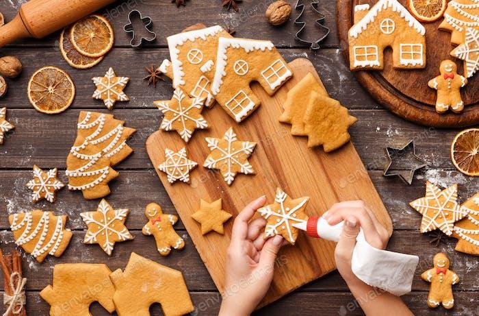 Vereisung Prozess der Weihnachtsbäckerei. Unerkennbare Frau Dekoration hausgemachte Kekse