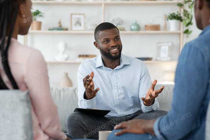 Confident black family counselor talking with married couple, giving advice to spouses