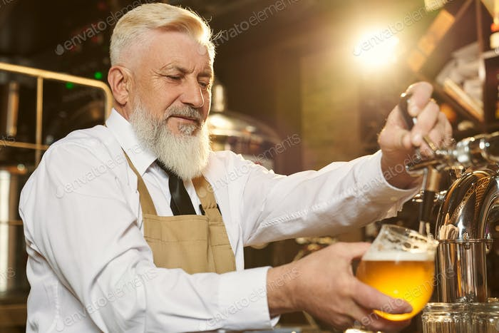 Barman pouring light beer in glass with beer tap