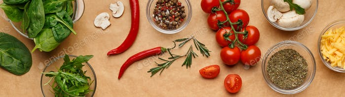Spices and ingredients for homemade pizza on wooden table