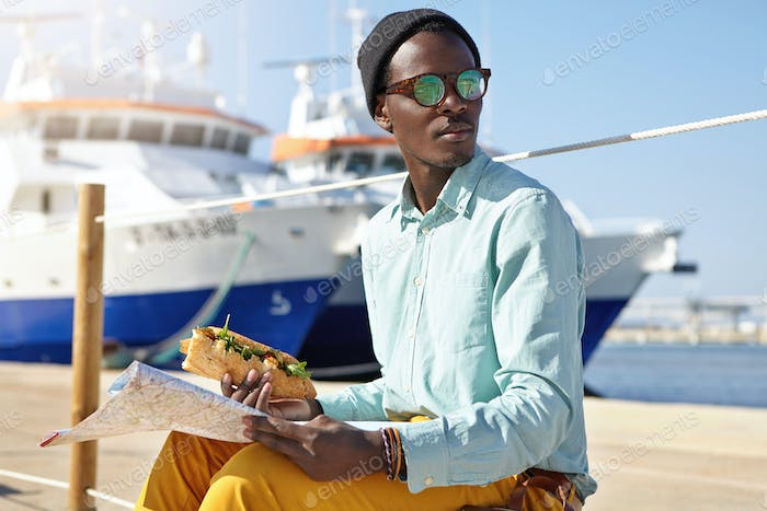 Fashionable young African American male tourist wearing stylish clothing and accessories traveling a