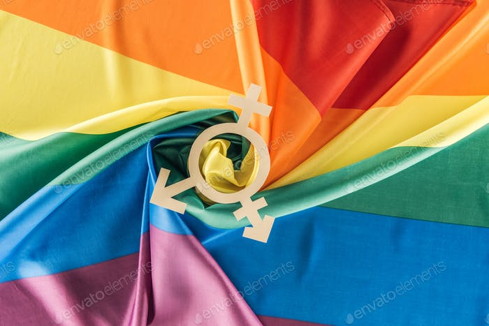 vista superior de la bandera arcoiris arrugado en forma de espiral con signo de género, concepto lgtb