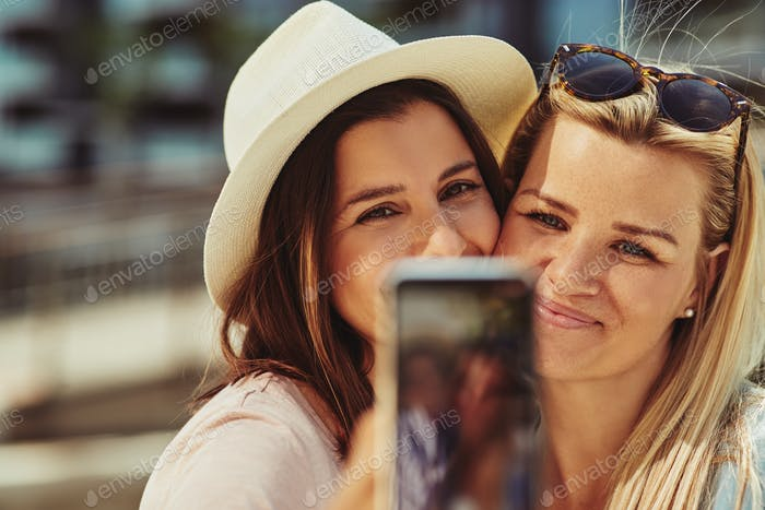 Two smiling female friends taking selfies together outside in summer