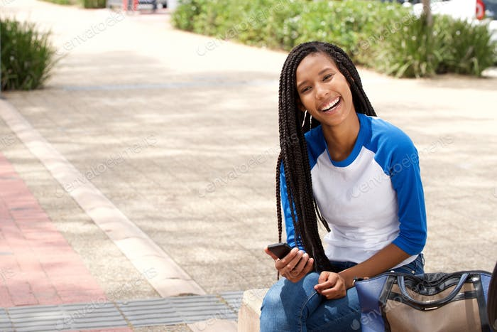 attractive young african woman sitting outside with smart phone and smiling