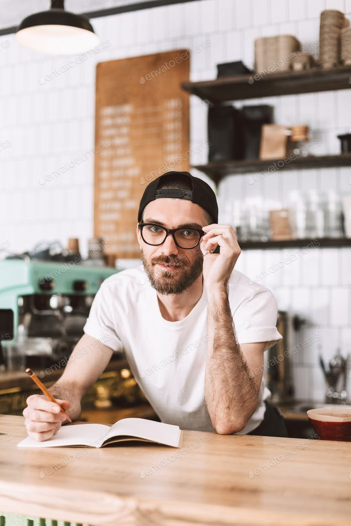 Smiling man in eyeglasses behind bar counter making notes happily looking in camera working in cafe