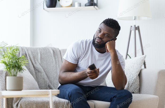 Bored african guy sitting at home, switching tv for film