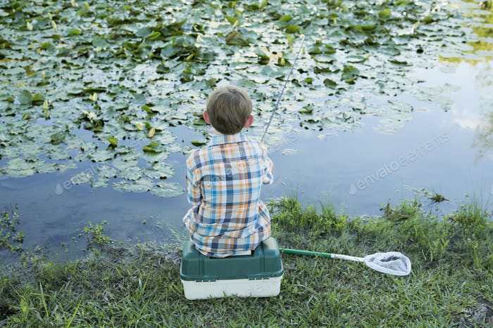Back view of a young boy sitting on his baitbox, fishing in the river.