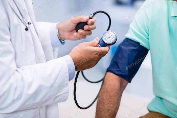 Mittlerer Abschnitt des Arztes, der den Blutdruck eines Patienten überprüft