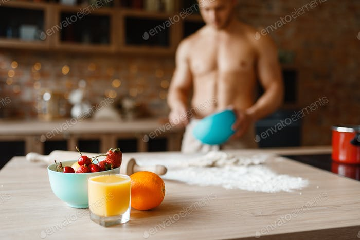 Nude man cooking dessert on the kitchen