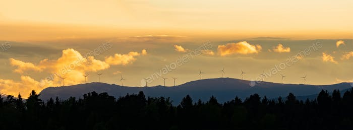 Windmills at Sunset against orange sky in Austria. Panorama