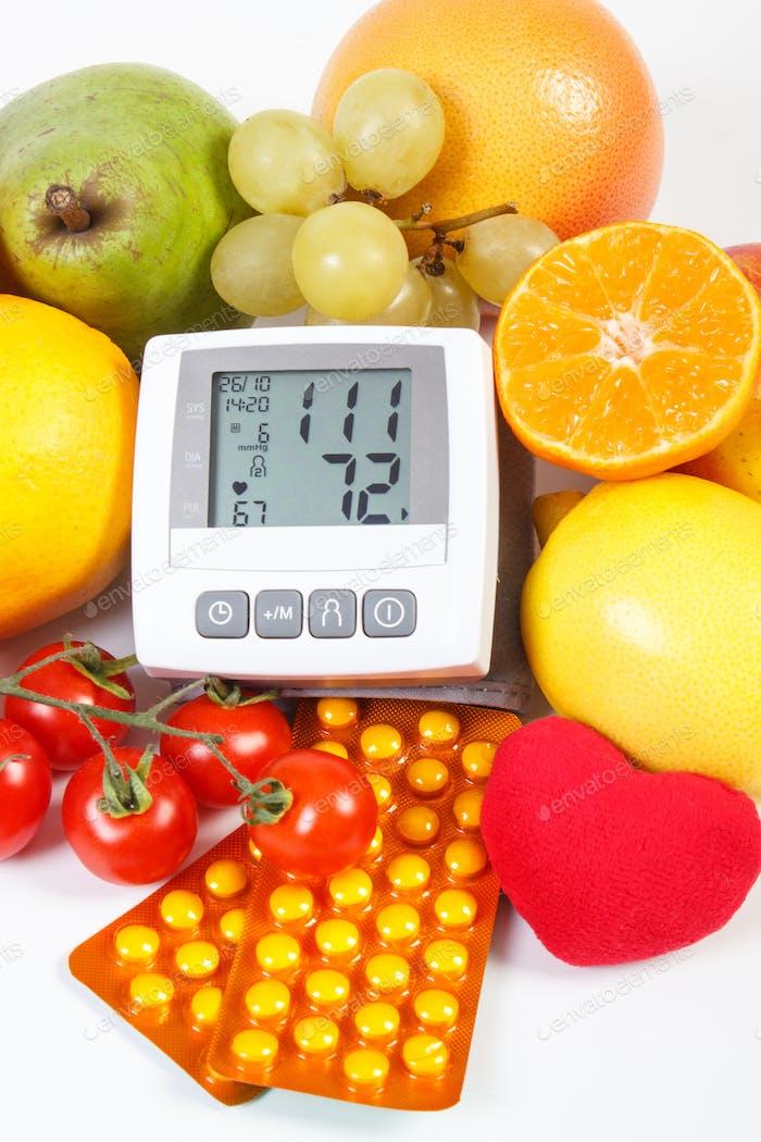 Blutdruckmessgerät, Obst mit Gemüse und medizinischen Pillen