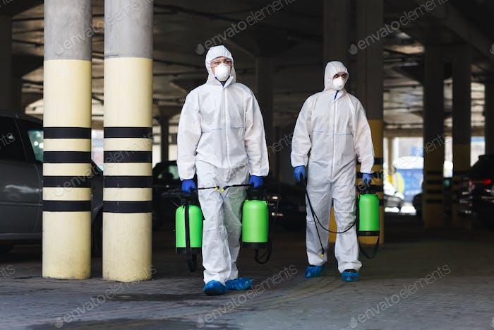 Hombres en trajes coronavirus celebración de productos químicos de desinfección al aire libre