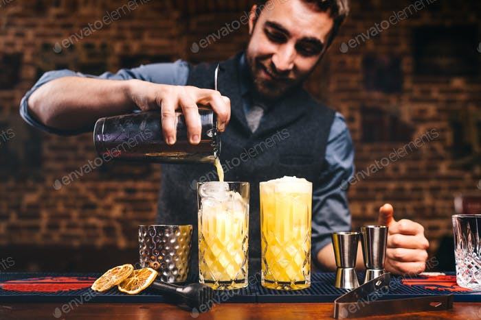 Professional barman preparing cocktails and pouring fresh alcohol in glasses.
