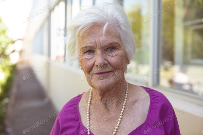 Portrait of happy Caucasian senior woman smiling while standing at nursing park