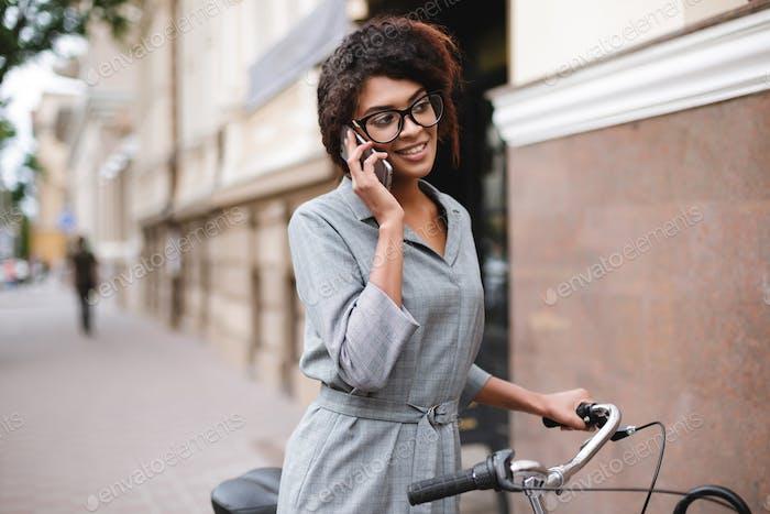 Fröhlich Afroamerikanerin Mädchen in Brille stehend mit Fahrrad und sprechen auf ihrem Handy