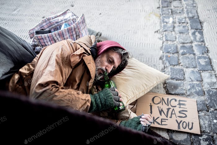 A top view fo homeless beggar man lying on the ground outdoors in city, drinking.