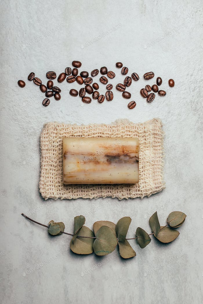 Piece of soap on natural bag with coffee beans and eucalyptus branch on rustic grey background.