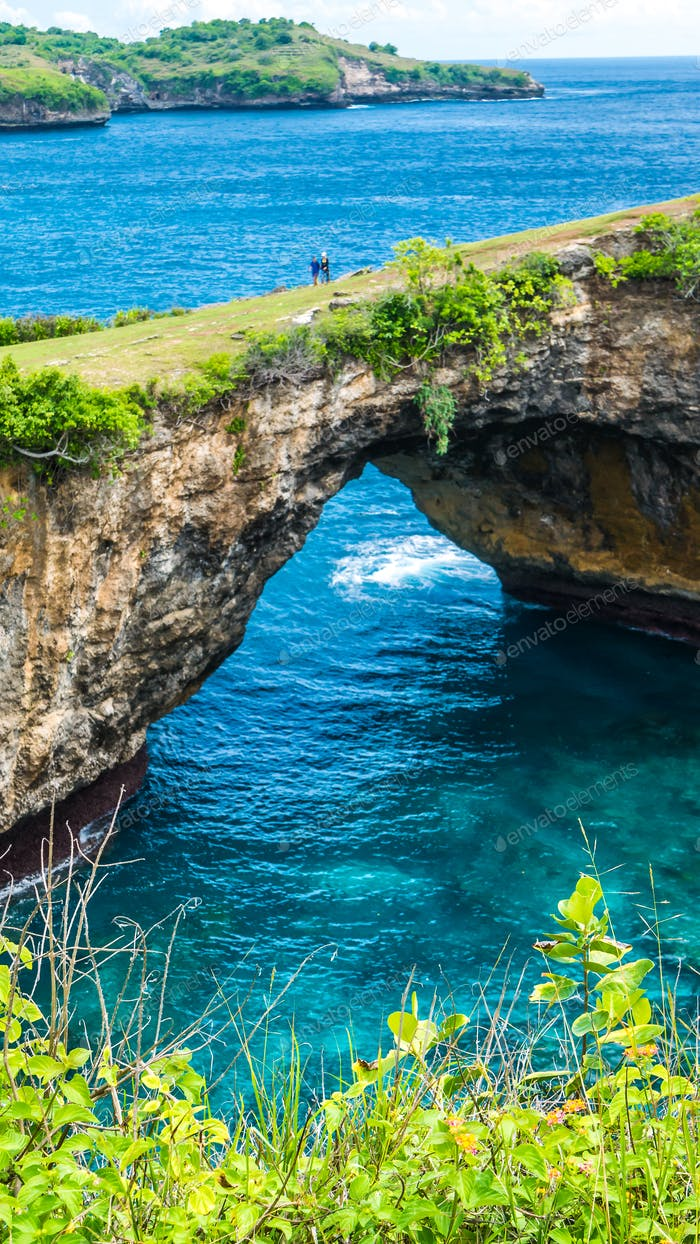Steinbogen über dem Meer. Gebrochener Strand. Felsküste. Nusa Penida, Indonesien