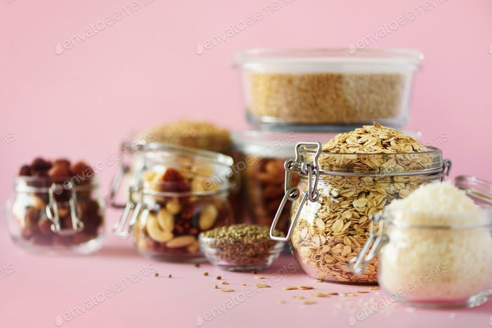 Vegan health food over pink background with copy space. Nuts, seeds, cereals, grains in glass jars