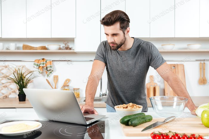 Man looking recipe on laptop in kitchen at home