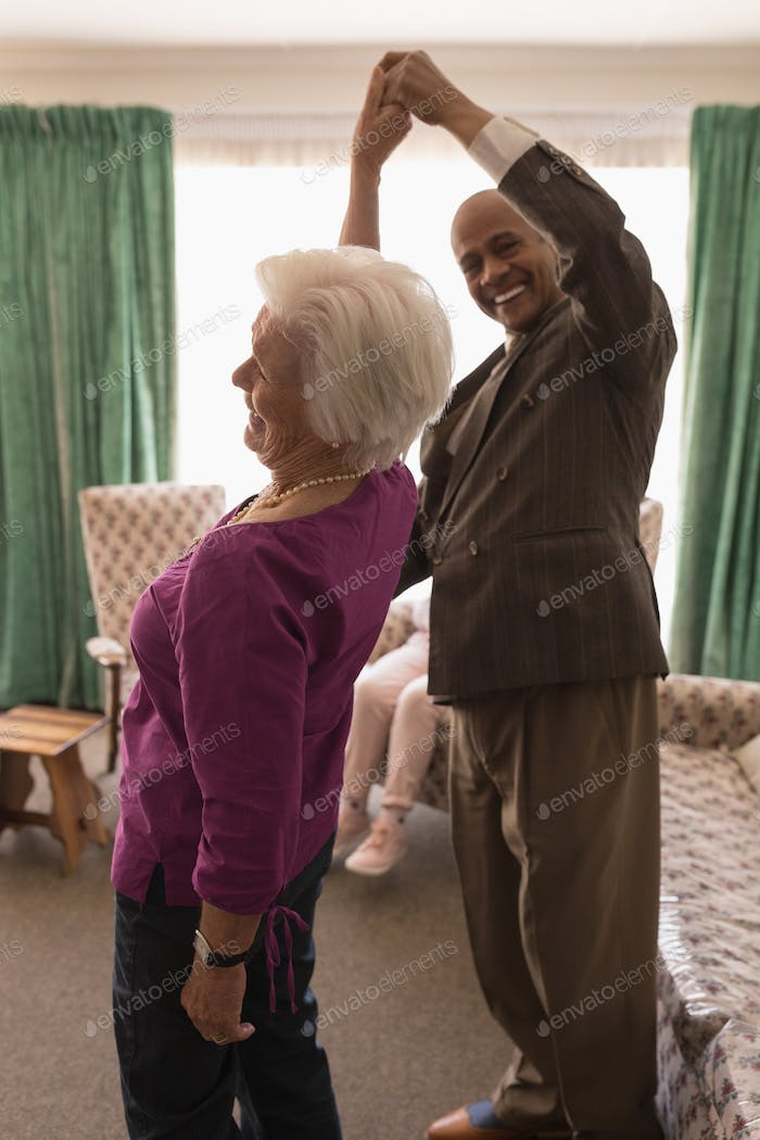 Side view of happy senior couple dancing with woman turning together at home