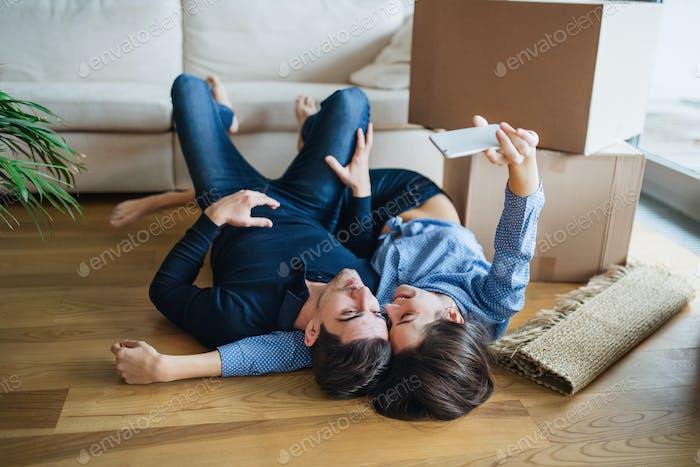 Una joven pareja con un teléfono inteligente moviéndose en un Novedad Página de inicio, Encantador selfie.