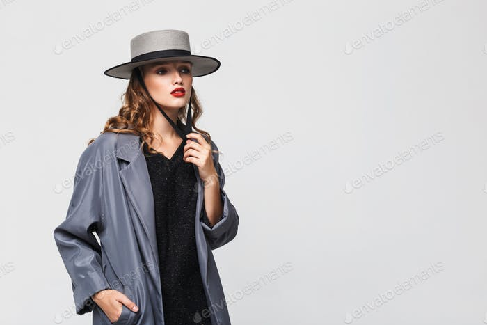 Attractive pensive woman with wavy hair in modern hat and cloak dreamily posing over gray background