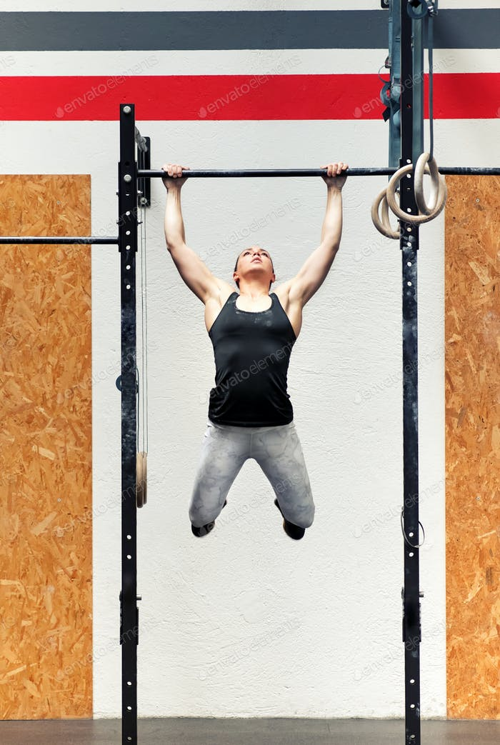 Young girl athlete doing pull-ups on a bar