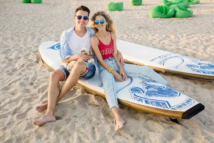 young attractive smiling couple having fun on beach playing with dogs