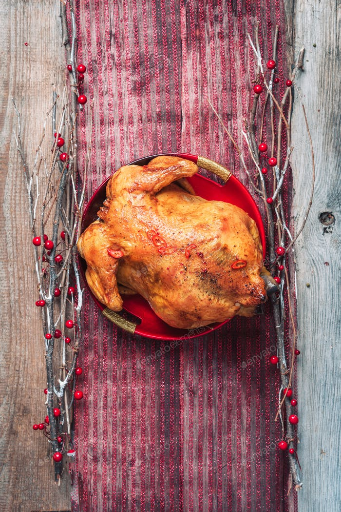 Roasted whole chicken with Christmas decoration on wooden background. Top view, copy space. Healthy