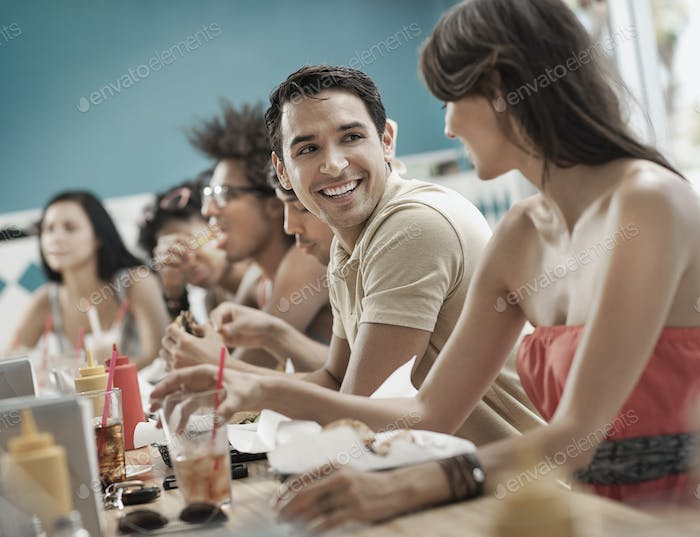 A group of friends, young men and women at a diner.