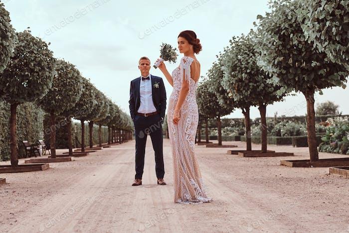 Full body portrait of newlyweds posing in the beautiful garden.