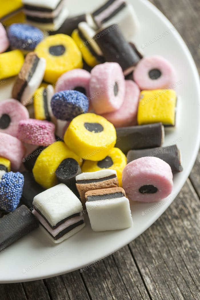 Mixed liquorice candies on plate.