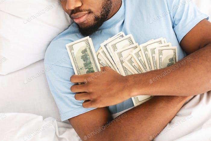 Hombre durmiendo con un montón de billetes de moneda