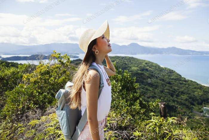 Japanese woman wearing hat and carrying backpack standing on a cliff, ocean in the background.