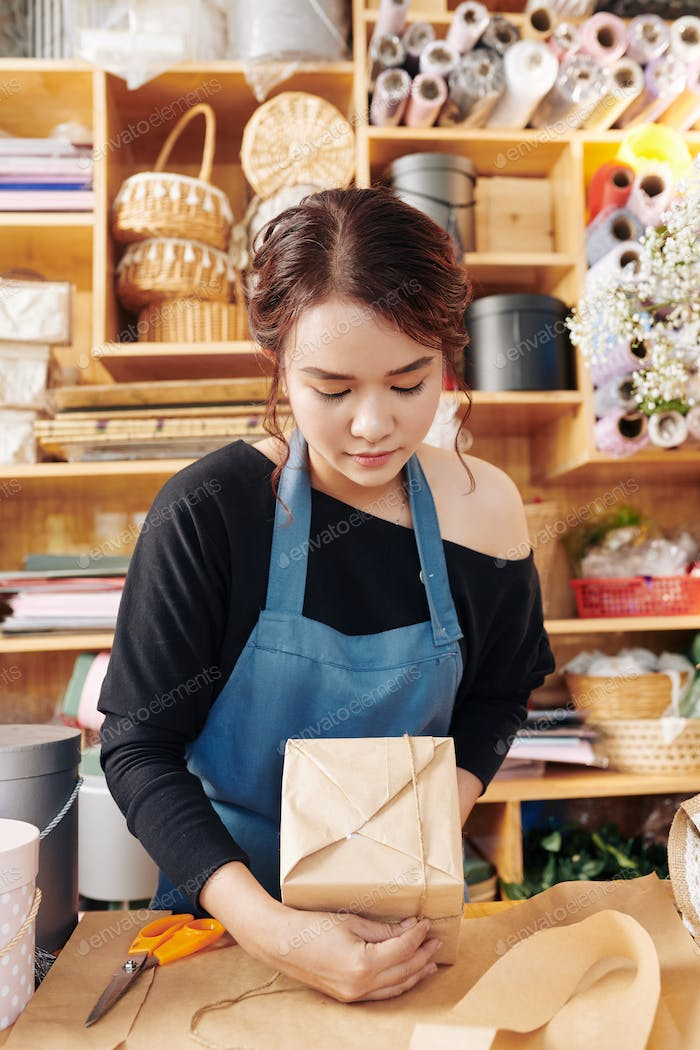Florist concentrated on wrapping present