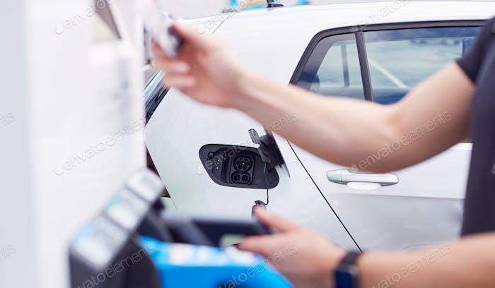 Hombre Carga Vehículo Eléctrico Pagando De Energía Con Tarjeta De Crédito En Estación De Carga
