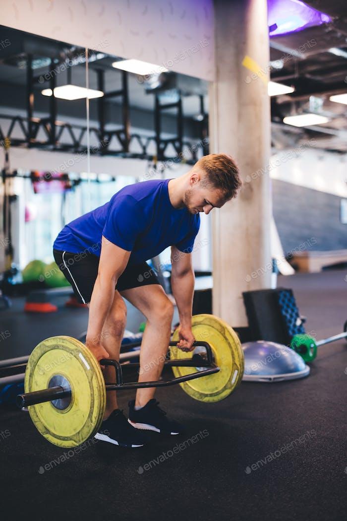 Мускульный человек поднимает тяжестей в тренажерном зале.