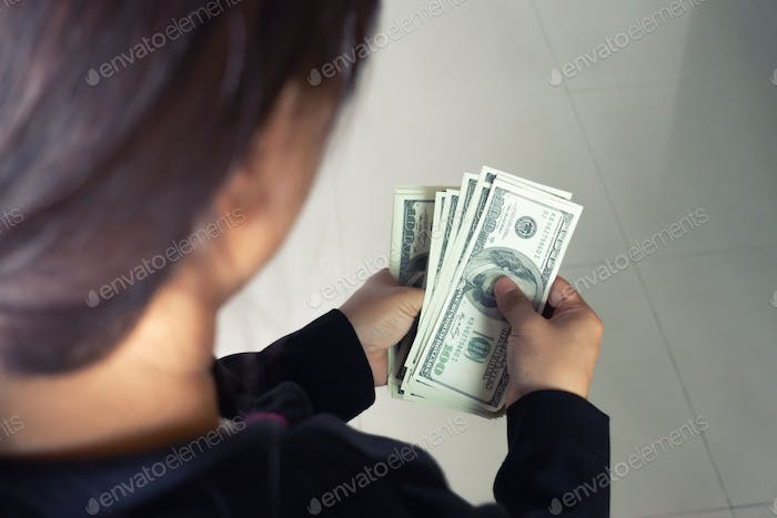 woman taking out money dollar banknotes from wallet
