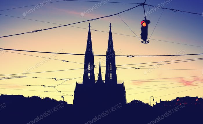 Silhouette of the Votive Church and stoplight at dusk.