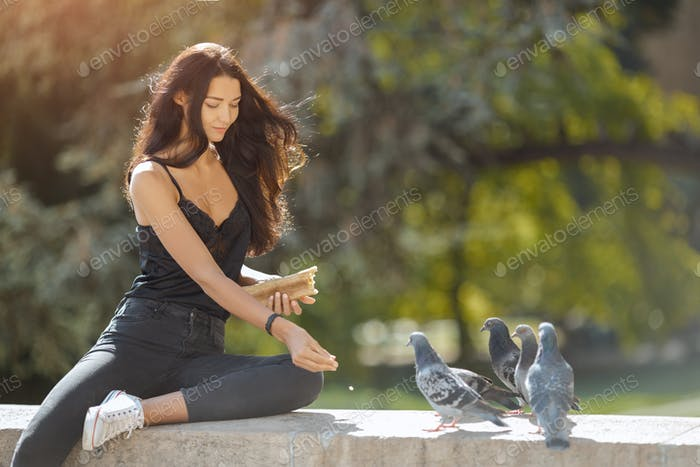 Beautiful young girl feeding pigeons