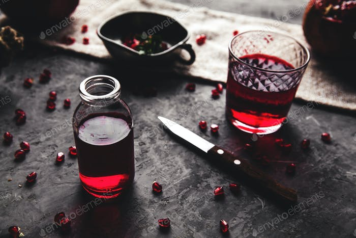 Red pomegranate juice in a glass, ripe and cut pomegranate and a sprig of mint on a gray