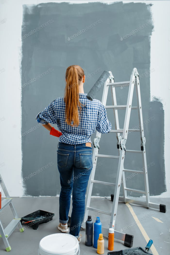 Female house painter looking on wall, back view
